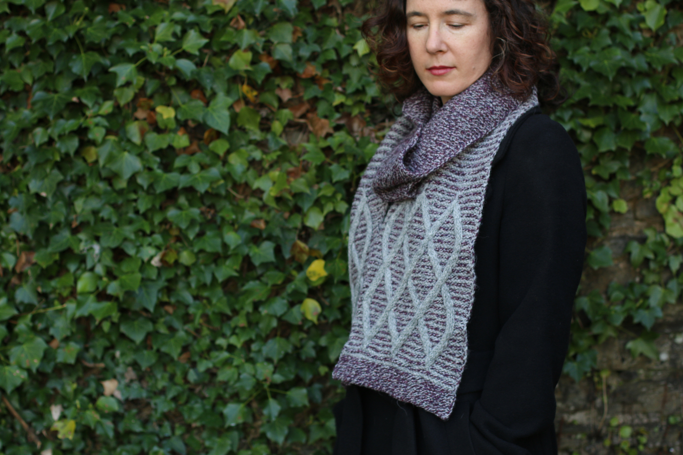 image of woman looking down while wearing cables scarf