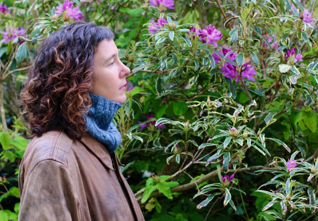 woman looking at flowers while wearing a light blue knitted cowl