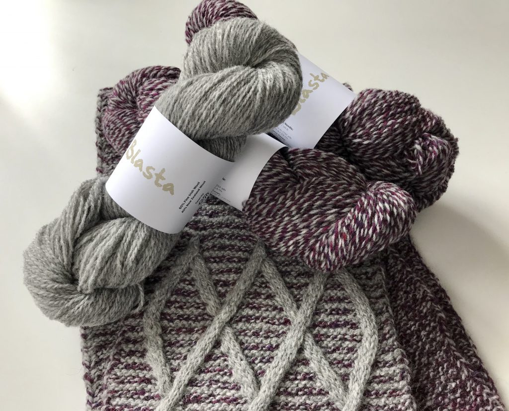 3 skeins of yarn shown over a cabled scarf