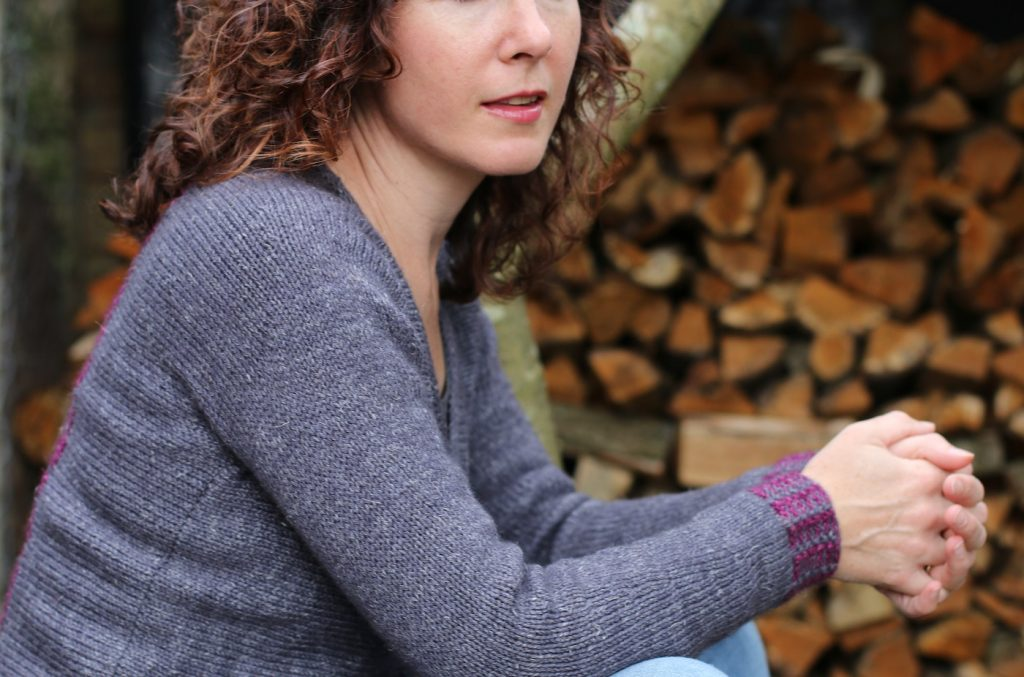 woman looking to the side wearing a grey cardigan