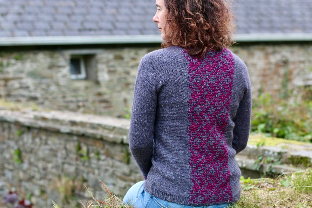 image of womans back with cardigan in dark grey with a pink and grey central stitch paneln