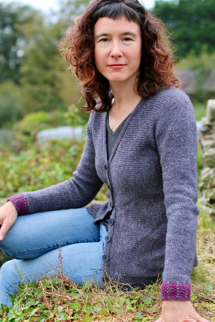 image of woman looking at camera wearing a dark grey cardigan