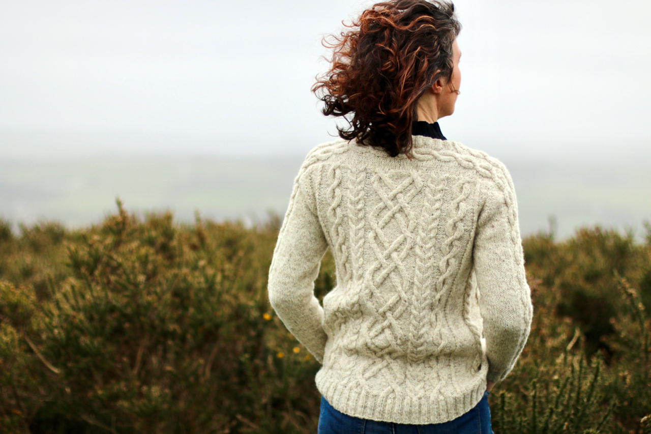 back of woman on hill in wind wearing cream cabled cardigan