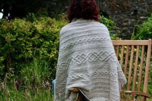 back of woman on chair with a cream aran blanket over her shouders