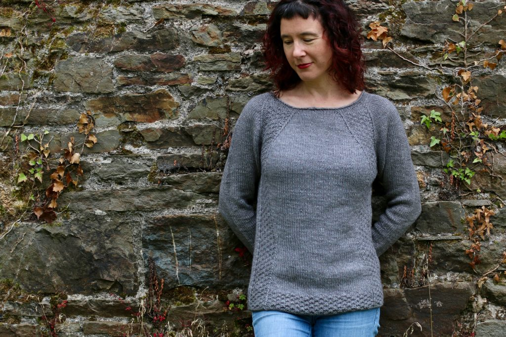 woman in front of stone wall, wearing grey sweater and looking down