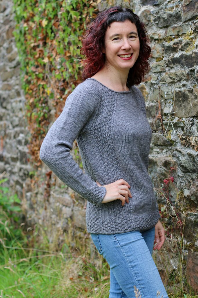 image of woman smiling in grey sweater with hand on her hip
