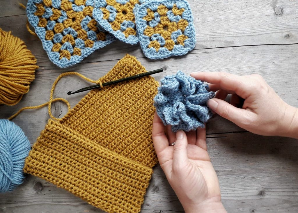 blue ruffley flower held in 2 hands