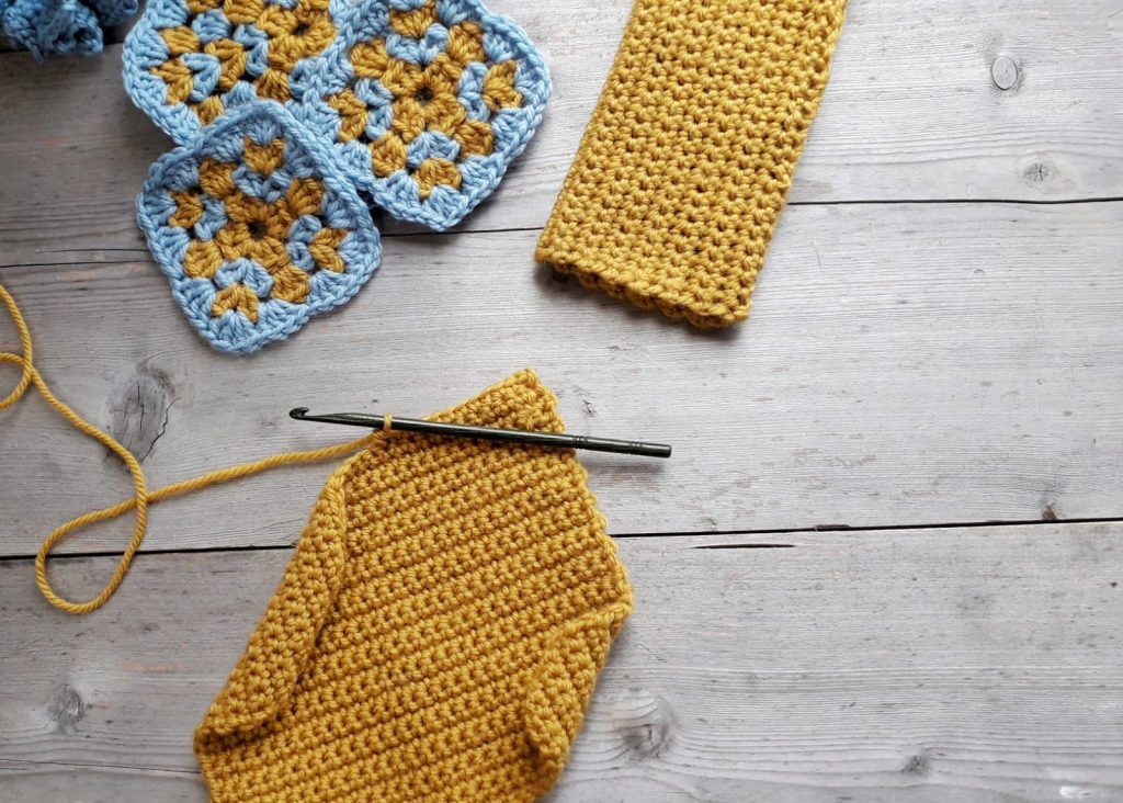 yellow crocheted square with finished mitten and crochet hook