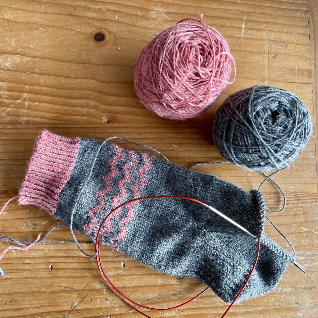 partially knit sock with 2 balls of yarn above it