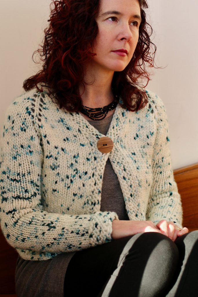 woman looking up while seated and wearing a white cardigan with speckles fastened with one large wooden button.