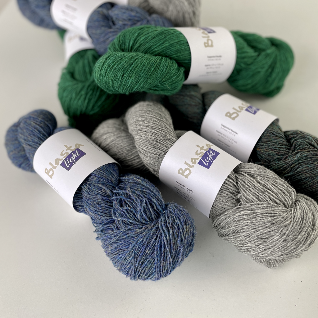 yarn of different colours in a pile on a white table