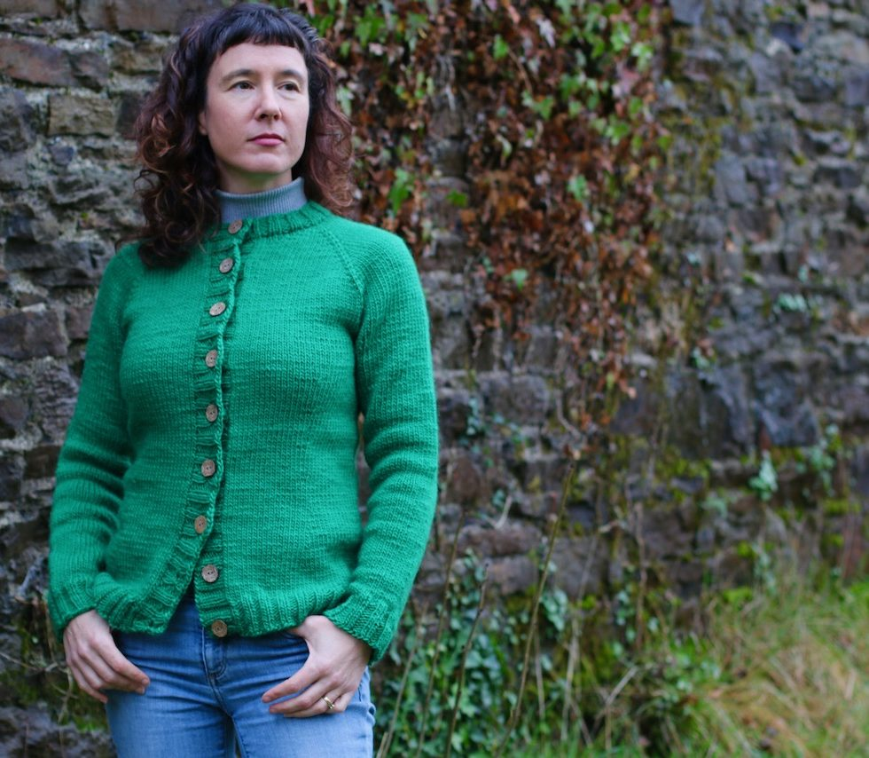 image of woman in green cardigan in front of stone wall