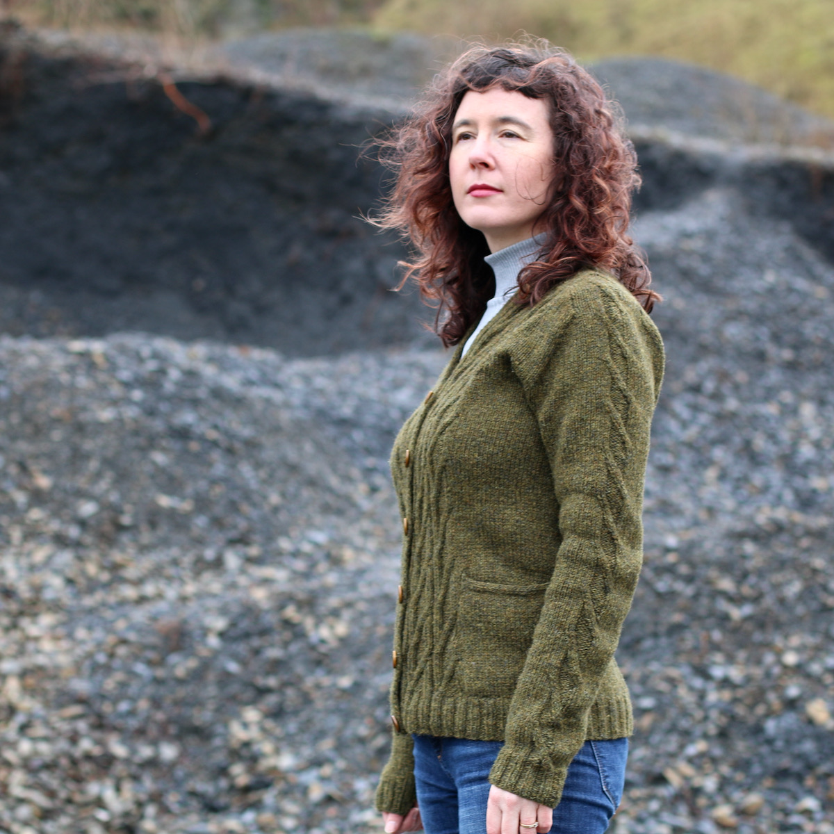 woman in green cardigan looking to side with pile of stones behind her