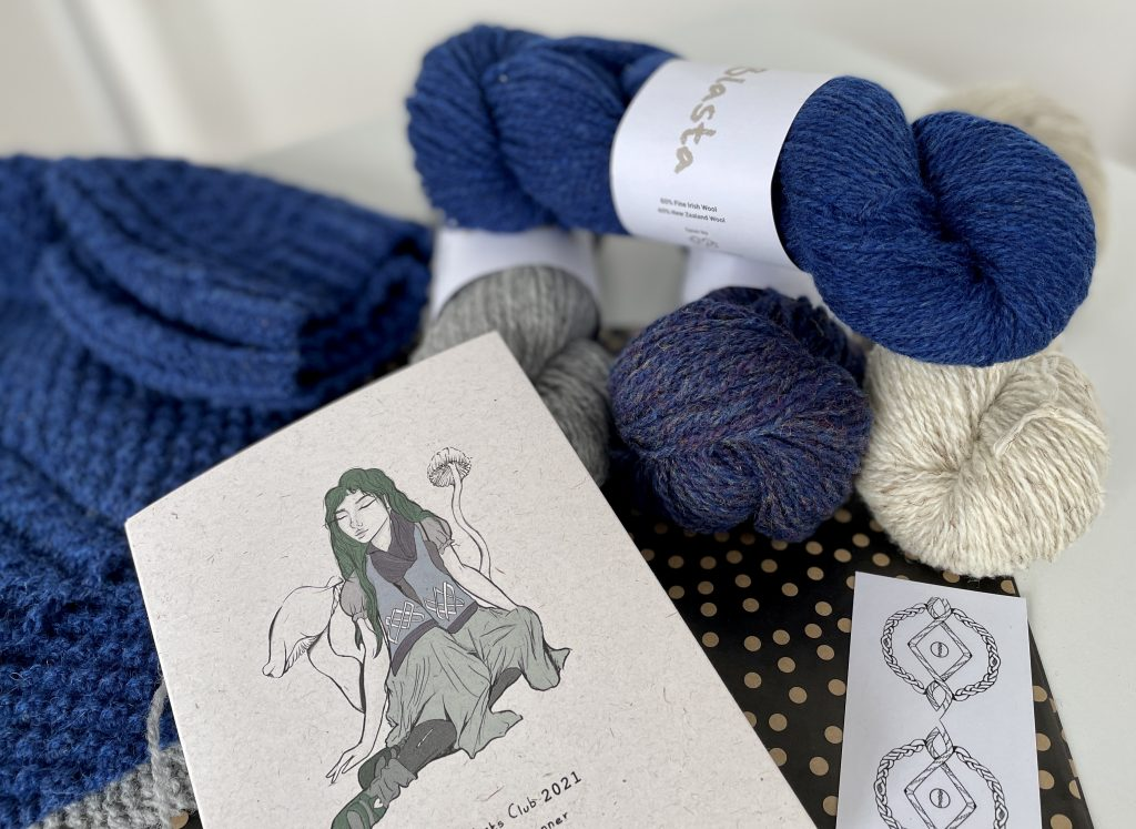 a pile of yarn skeins in the top. A notebook with an image of a girl sitting in front. Pile of knitting in the background