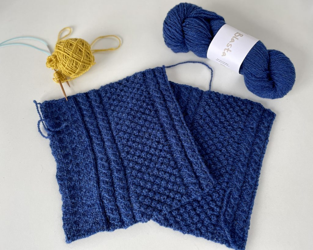 two blue squares of knitting with a skein of blue yarn over them and yellow yarn wound with needles