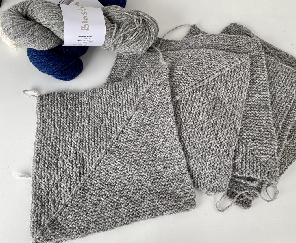 pile of square grey garter stitch knitting with a skein of grey and navy yarn above.