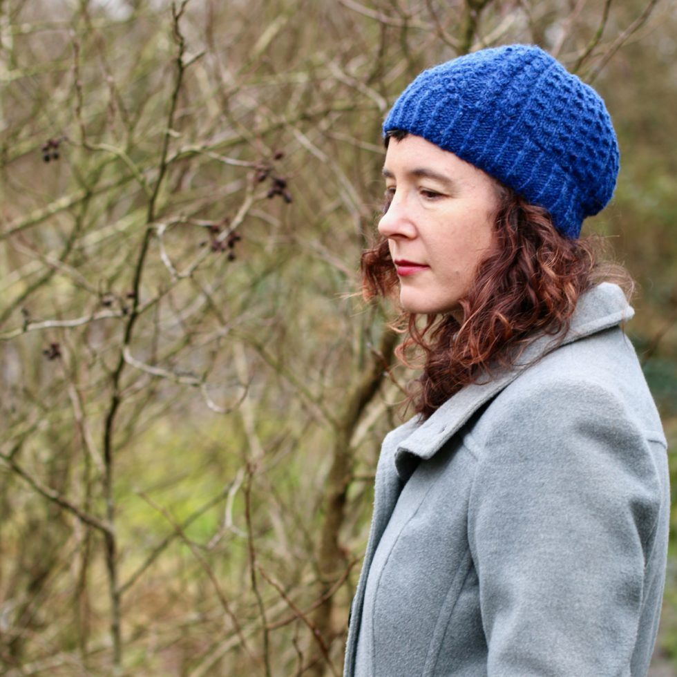 woman in grey coat looking sideways and wearing a bright blue hat. Branches behind her.