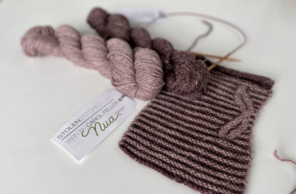 striped knitting with cable and two skeins of yarn in pink and purple shade