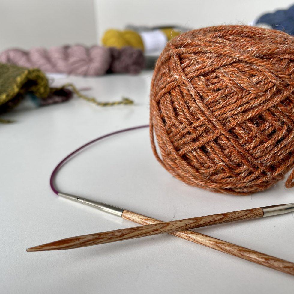 image of orange yarn with needle on table