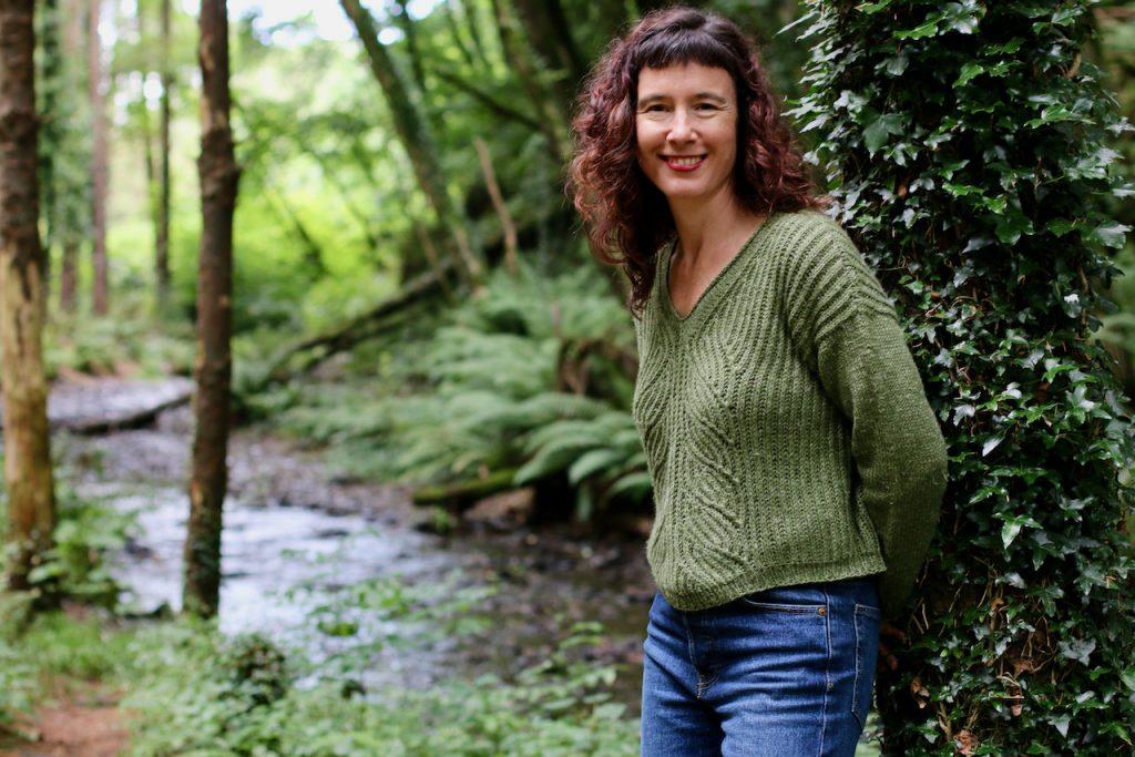 Carol Feller wearing a green brioche handknit sweater in the woods