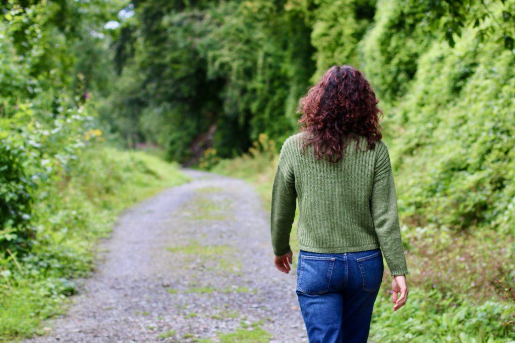 Carol Feller wearing the handnit Brutach sweater walking in the Irish woods