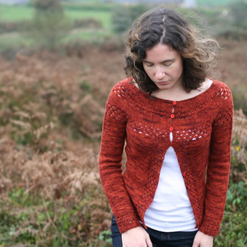 Red Cardigan by Stolen Stitches worn by a woman walking in a field in autumn.