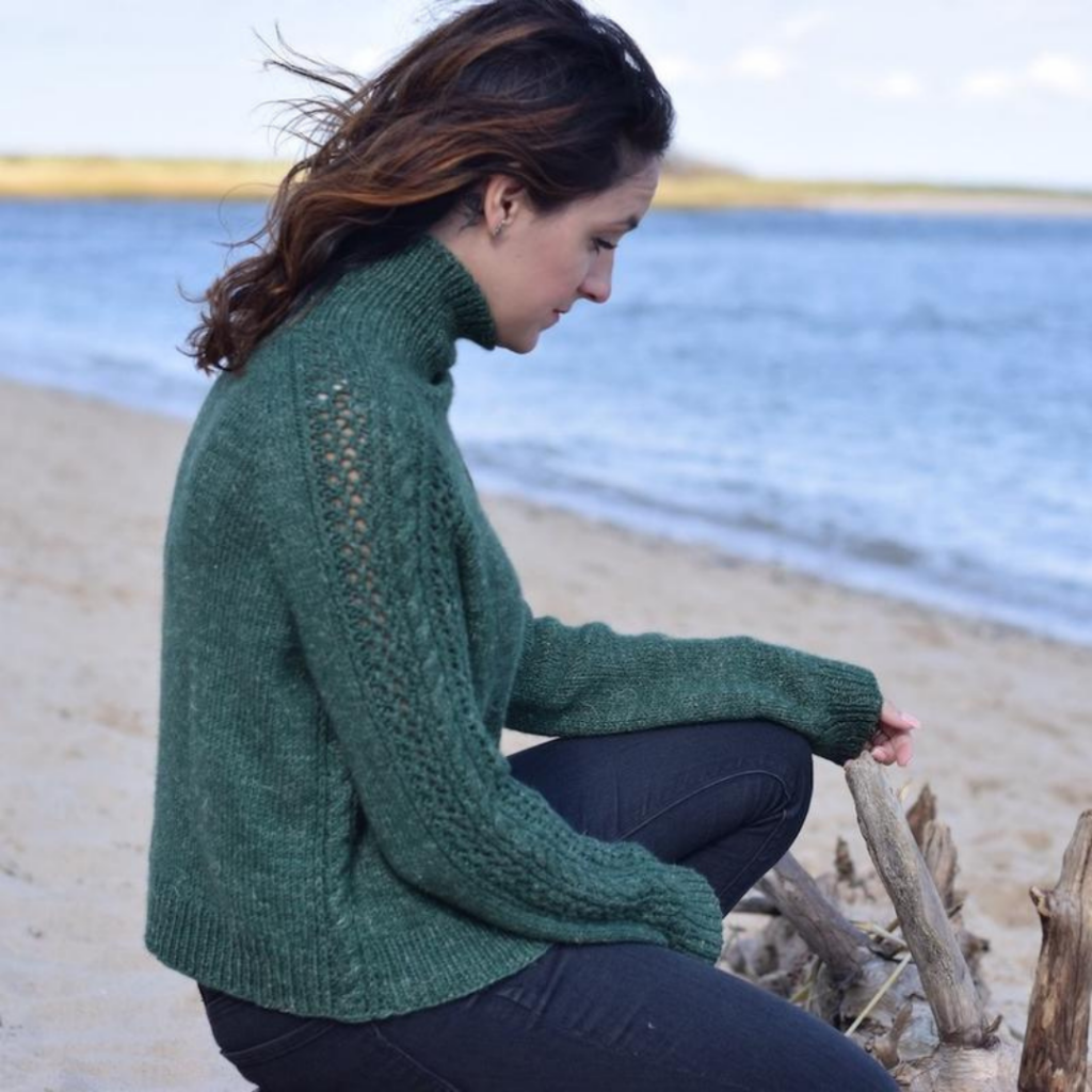 Woman sitting on the beach in agreen handknit sweater
