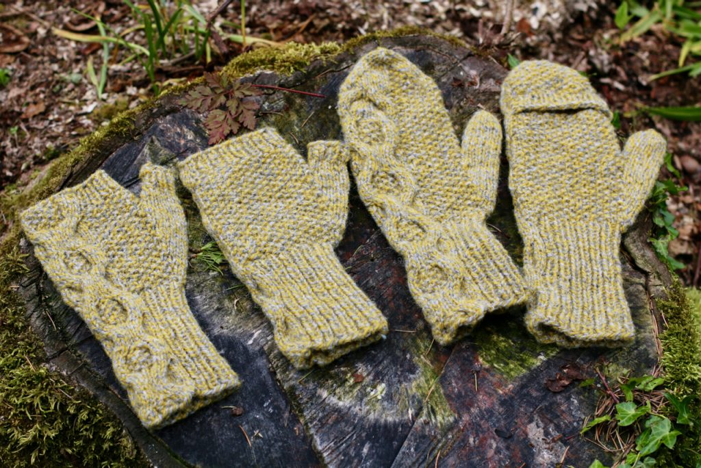 sAn image of 2 pairs of Hort mitts, one fliptop one fingerless displayed on a wooden stump.